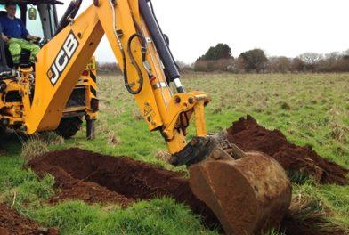 JCB digging trench in field
